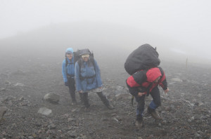 Sharron, Katy and WeiMin heading up to Syme Hut, WeiMin carrying his camera rugby style
