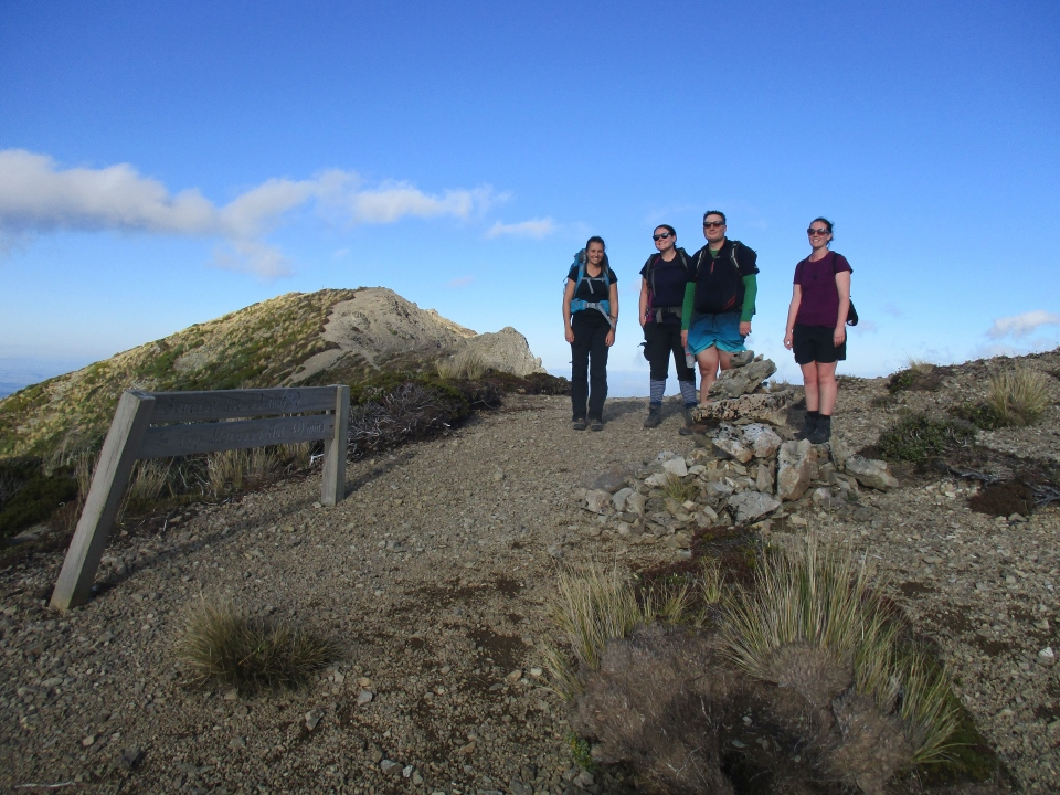 Trampers on a ridge near a sign in the Ruahine Ranges