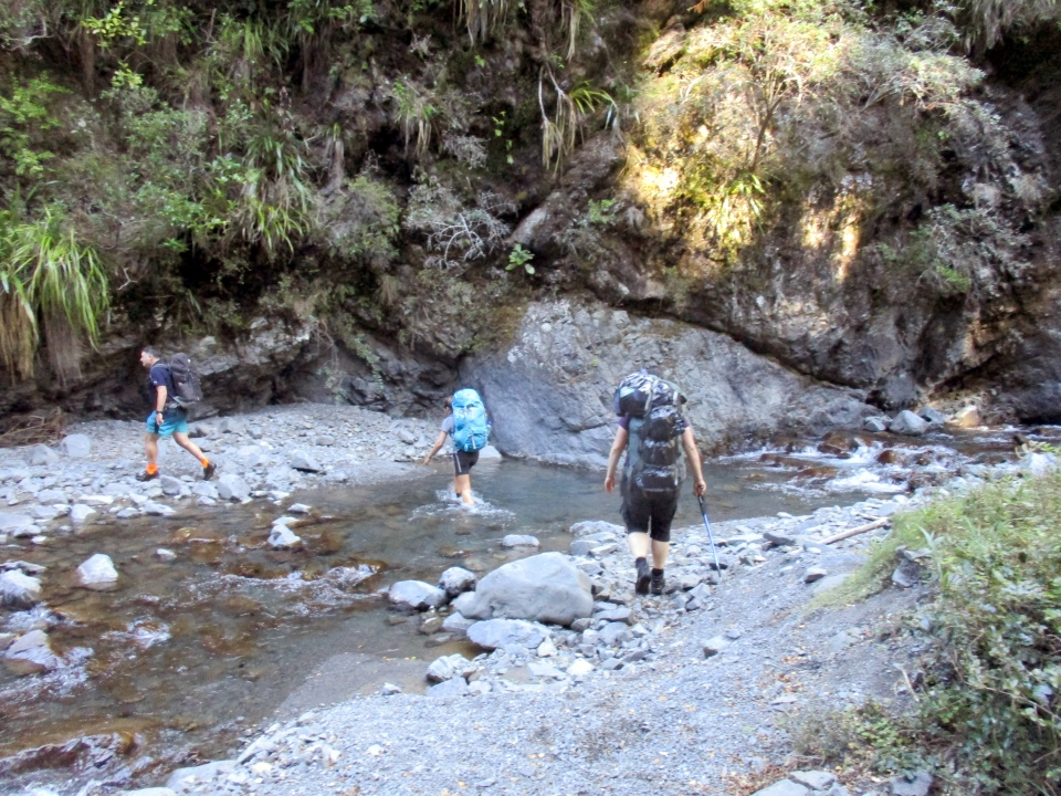 Trampers walk across a river in the Ruahine Ranges