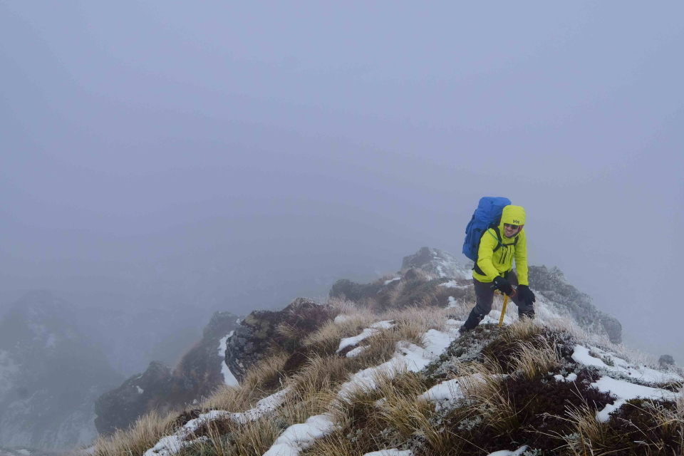 Tramper in low visibility on top of a ridge