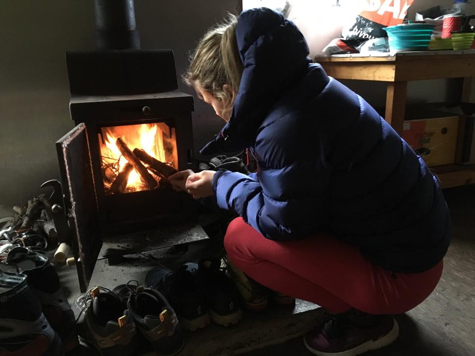 Woman lighting a fire inside a hut