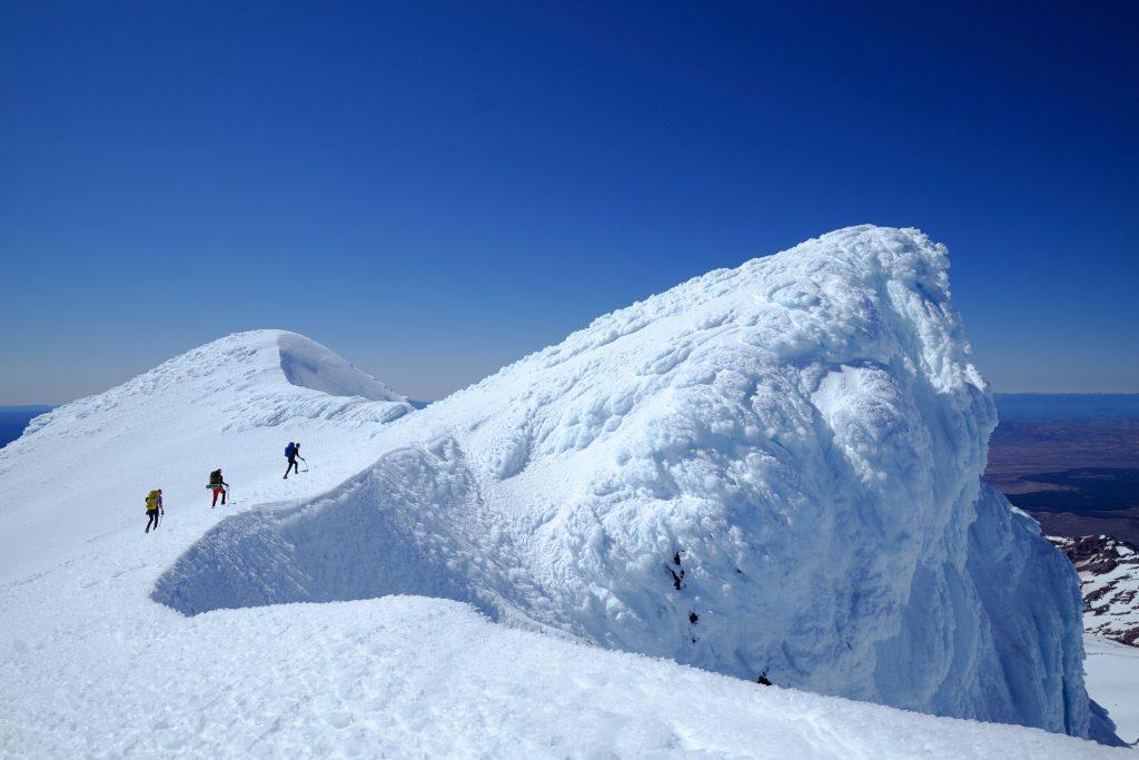Three people waking up Mt Ruapehu's crater rim