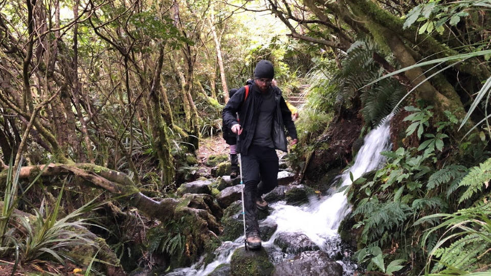 Tramper walking over a stream