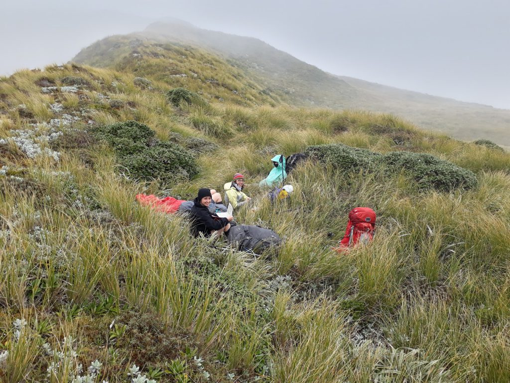 Jamie, Anna, and Loretha enjoy a welcome late lunch - tucked in out of the wind just below the ridge