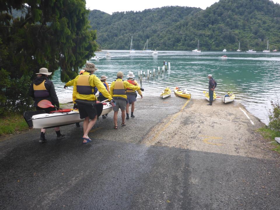 People walking a kayak into water