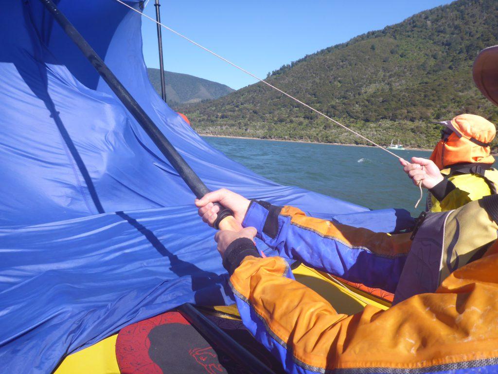 Kayakers improvising a sail from a tarpaulin