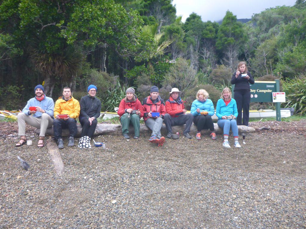 Group of nine people eating food on a log