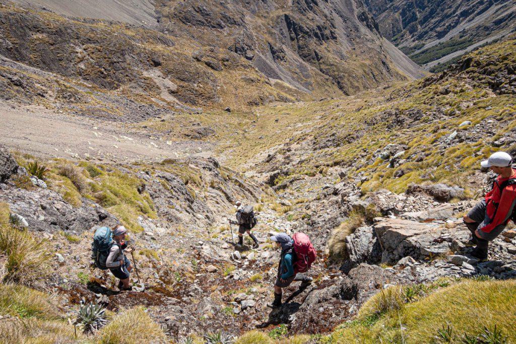 Four trampers cross a steep, dry creek bed