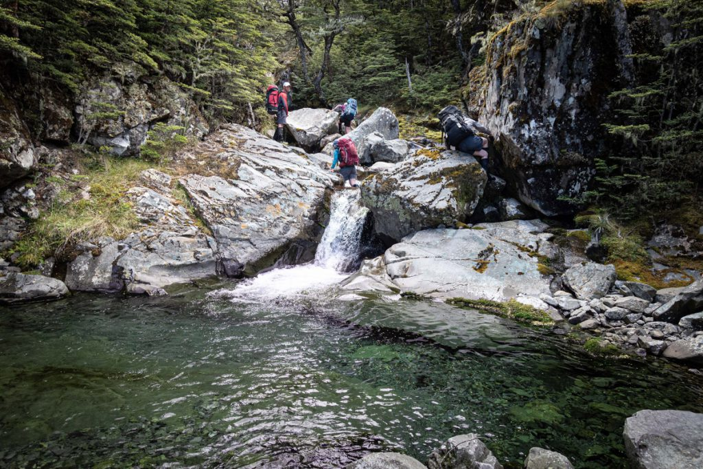 Trampers crossing a small waterfall with a pool below