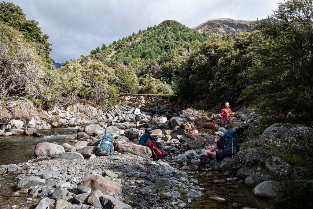 Trampers sitting in a rocky stream