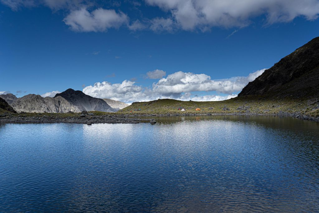View across a tarn to two tents with mountains in the background