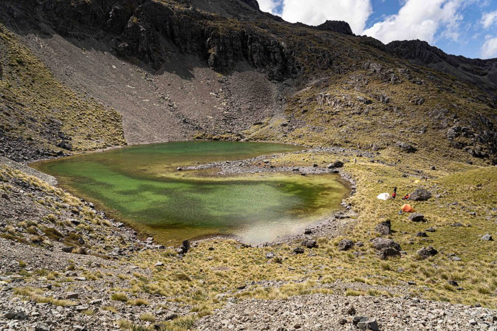 A green alpine tarn with two tents set up nearby