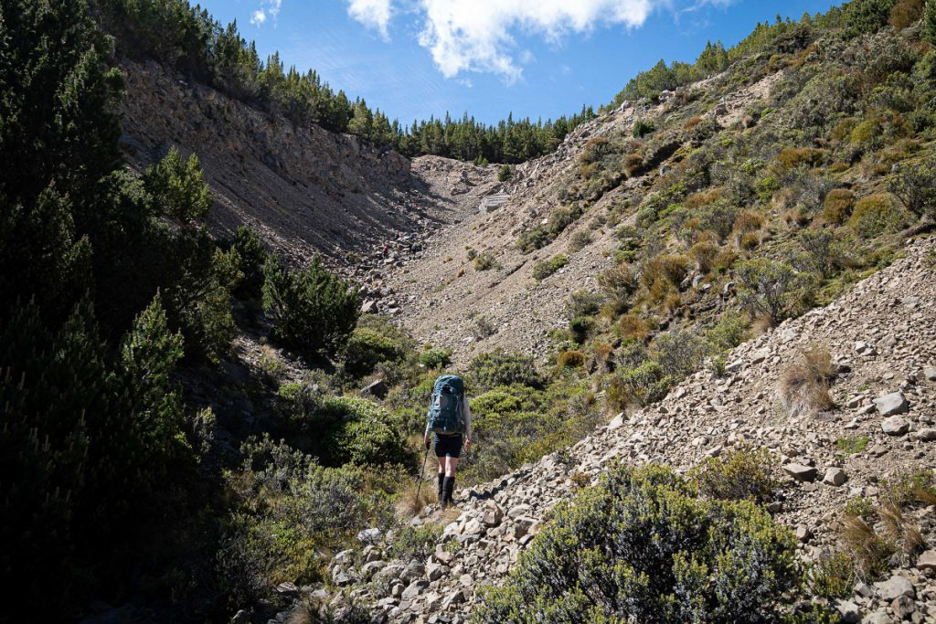 A tramper walks up a scree-filled valley