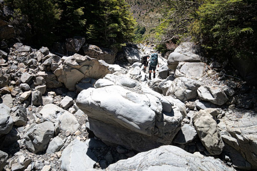 Two trampers follow a boulder-strewn dry creek bed