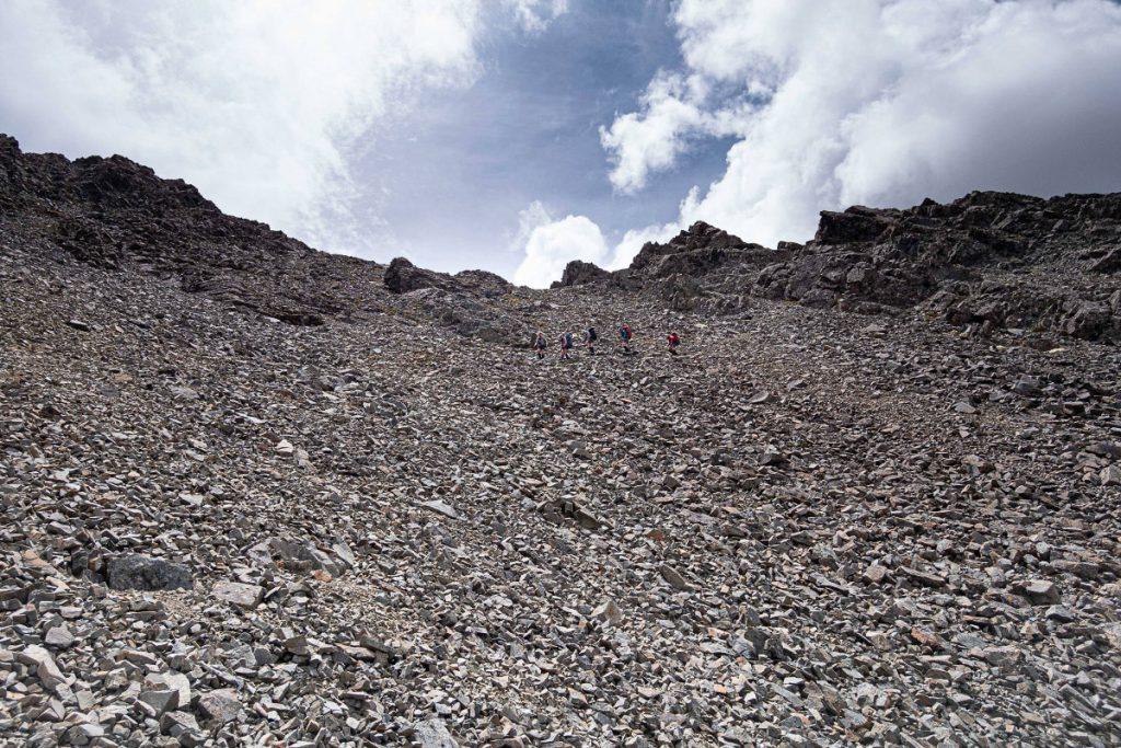 Five trampers descending a scree slope