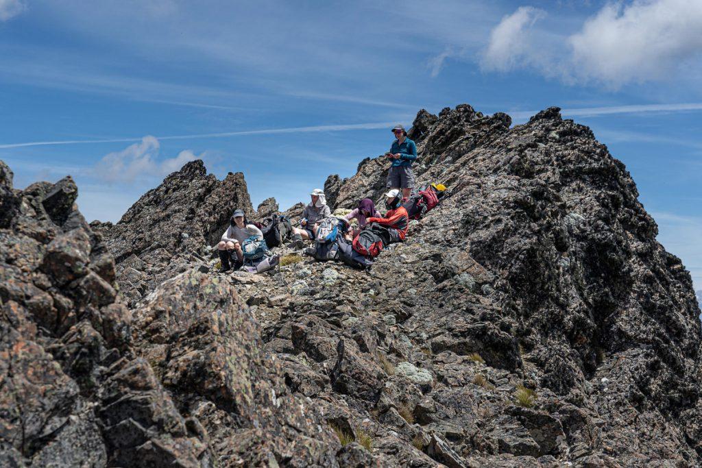 Five trampers resting on a rocky ridgeline