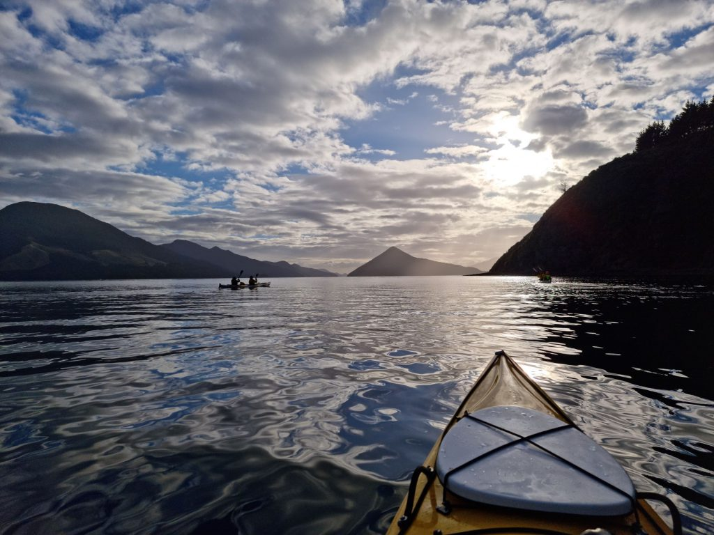 View over the prow of a kayak at sea, evening