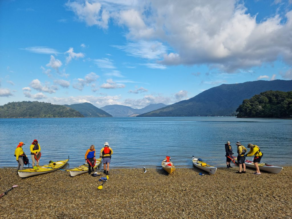 Seven people and five kayaks prepare to take to the water from the beach