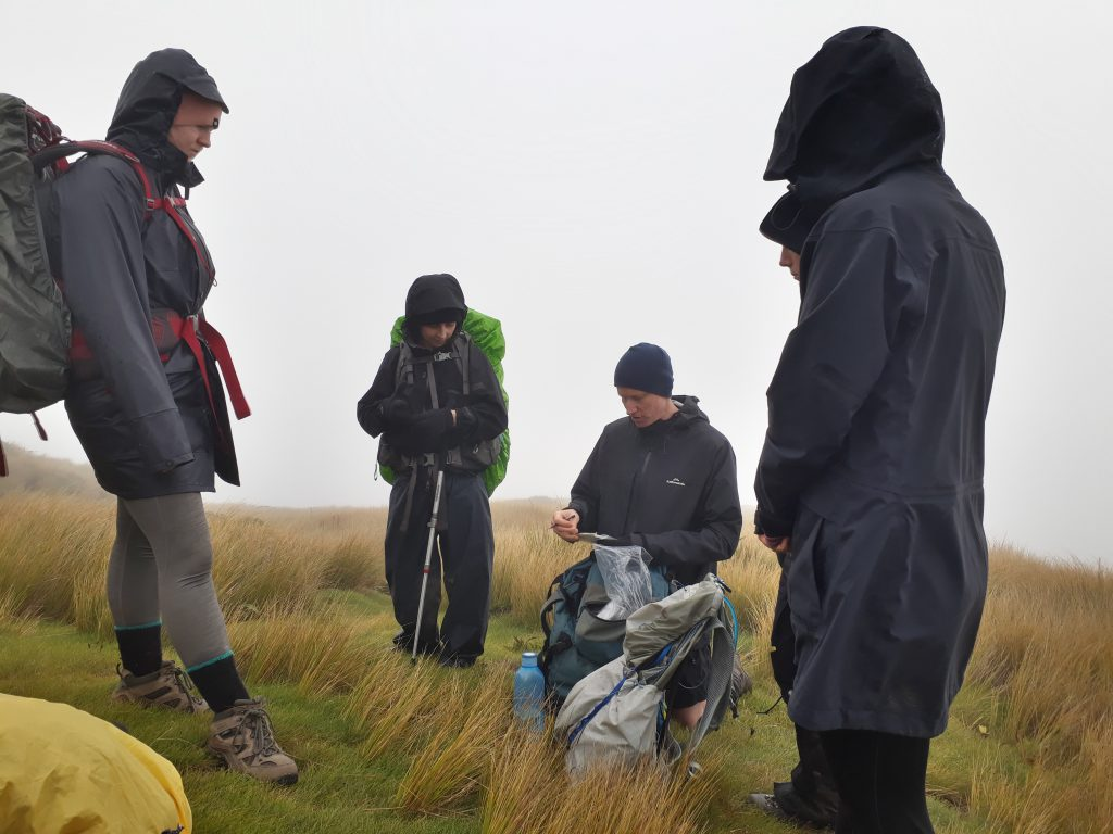 Nutter doing a crossword surrounded by trampers and fog