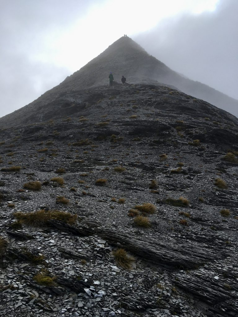 Two trampers descend from a peak in cloud. Two more remain on the summit