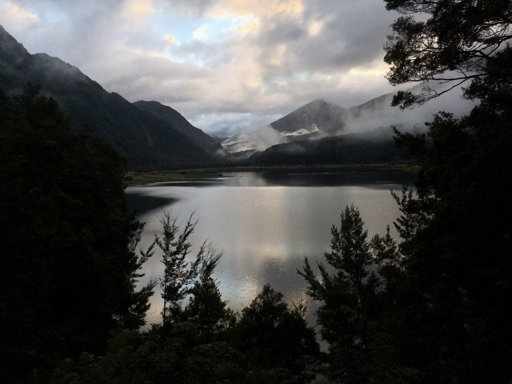 View over a lake with mountains and clouds. Trees in foreground