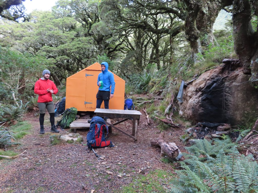 Two trampers by an orange bivvy
