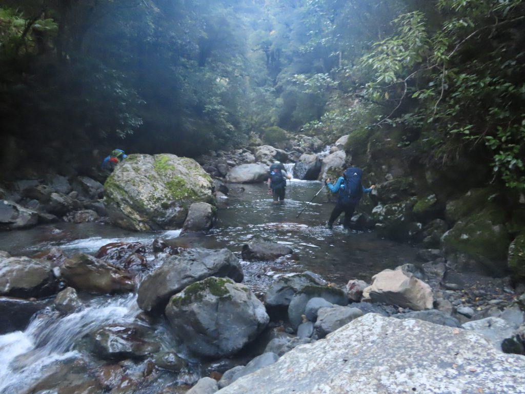 Trampers wading up a stream