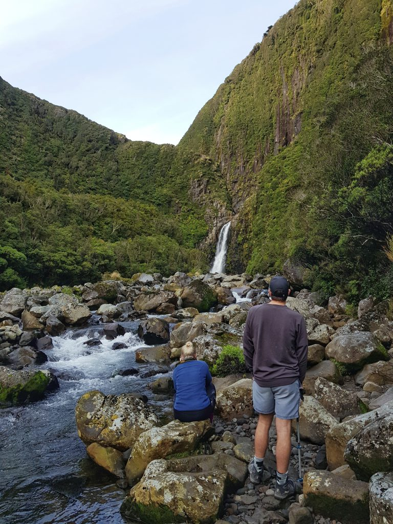 Two trampers looking at a small waterfall