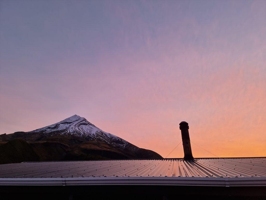Sunset over hut roof with Taranaki