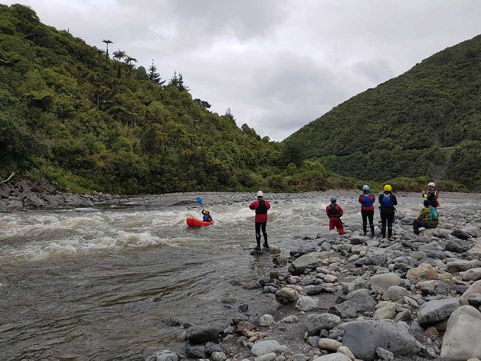 People watching a packrafter on a river
